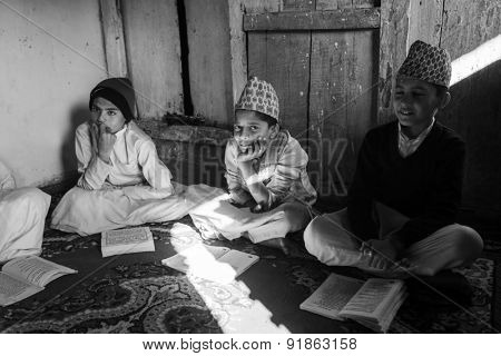 KATHMANDU, NEPAL - CIRCA DEC, 2013: Unknown children during the reading of texts in Sanskrit at Jagadguru School. School established at 2013 to let preserve Hindu culture.