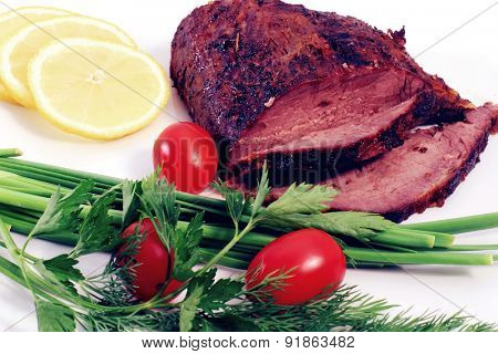 roast beef meat steak chunk with asparagus dill and cherry tomatoes on white plate