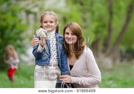 Young Woman Embraces Her Daughter With Dandelions