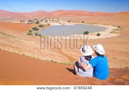 Travellers in Africa, couple on romantic vacation in Namibia, looking at beautiful Namib desert