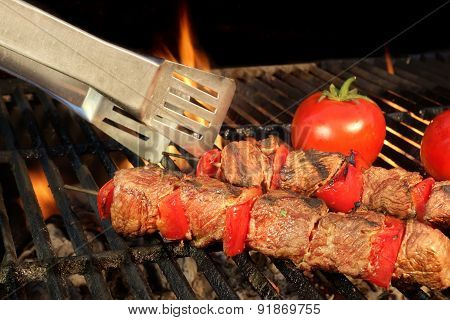 Tongue Hold Bbq Beef Shish Kebab With Vegetables On The Hot  Flaming Cast Iron Grill Close-up