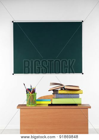 Wooden desk with stationery and chair in class on blackboard background