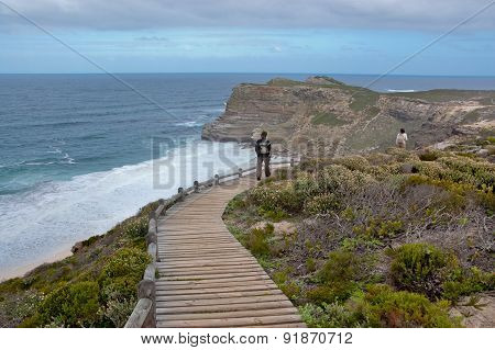 Tourist  on vacation walking on wooden path and looking at the beautiful view. Cliffs and ocean