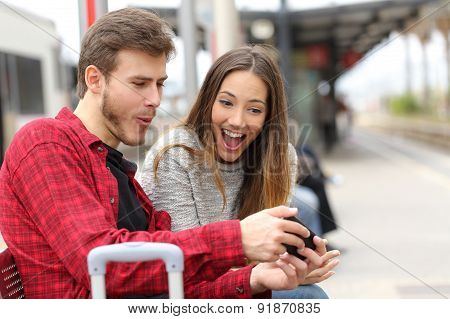 Couple Playing Games With A Smart Phone In A Train Station