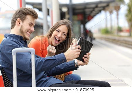 Euphoric Couple Playing Games In A Tablet In A Train Station