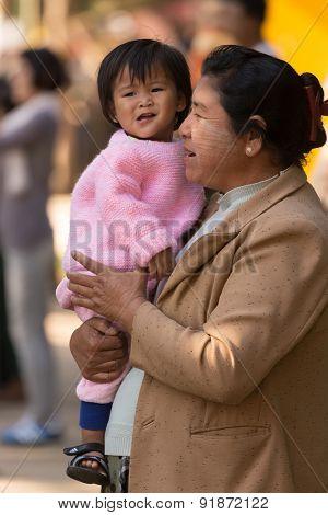 BAGAN, MYANMAR, JANUARY 22, 2015: A Burmese woman is holding her little daughter in a street of Bagan, Myanmar (Burma)