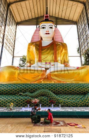 AMARAPURA, MYANMAR, JANUARY 20, 2015: Two mens are sitting below a huge and colorful Buddha statue in the Amarapura village near Mandalay, Myanmar (Burma)