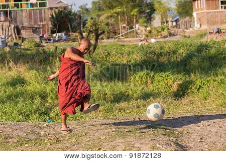 NYAUNG SHWE, MYANMAR, JANUARY 28, 2015:A buddhist monk is playing football under the sun near the Inle lake in Nyaung Shwe, Myanmar (Burma).