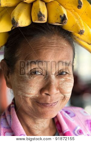 MANDALAY, MYANMAR, JANUARY 22, 2015: Portrait of a funny Burmese woman wearing a banana bunch on her head, in the slow boat from Mandalay to Bagan in Myanmar (Burma)