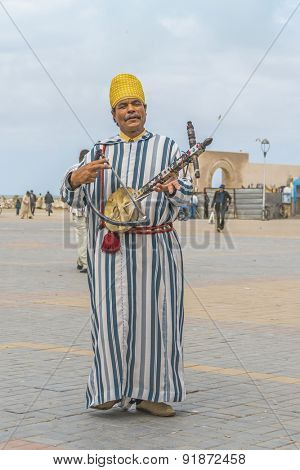 AS-SAWIRA, MOROCCO, APRIL 7, 2015: A local man plays traditional Berber instrument