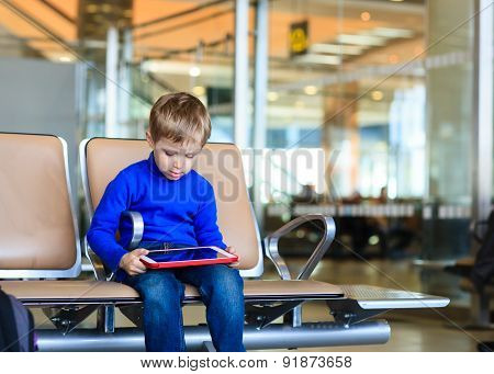 little boy looking at touch pad in the airport