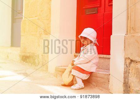 cute little girl waiting at the door on street of Malta