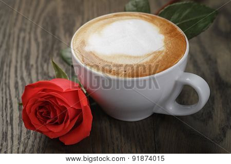 fresh cappuccino with red rose on table