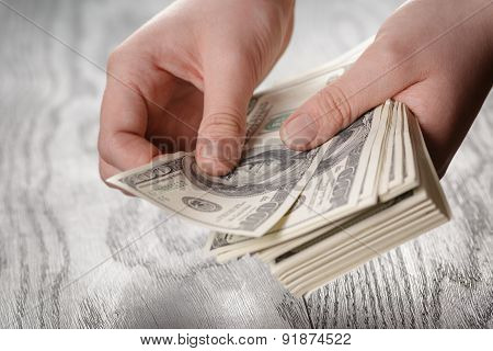 young female hands count dollar bills on wood table, closeup
