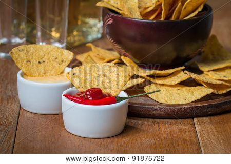 Mexican Nacho Chips, Cheese And Salsa Dip In Bowl And Tequila