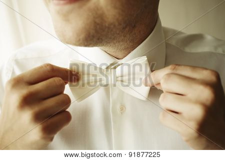 Handsome Businessman Fixes His Bow Tie