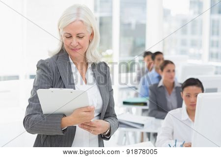 Businesswoman checking her clipboard while team work using computer in office