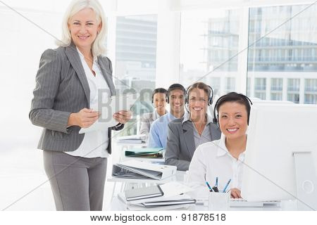 Smiling businesswoman looking at camera while work team using computer in office