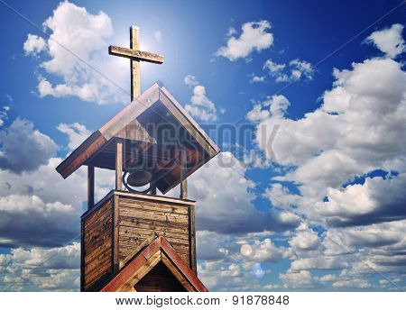 A Bell Tower With Cross And Heavenly Light