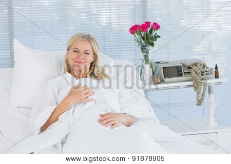 Smiling patient looking at camera on her bed in hospital