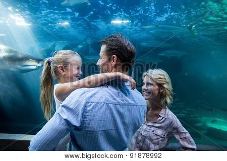 Familly enjoying behind a fish tank at the aquarium