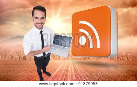 Smiling businessman pointing his laptop against sun shining over city
