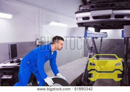 Mechanic holding tire on white background against auto repair shop