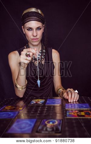 Fortune teller forecasting the future with pendulum on black background