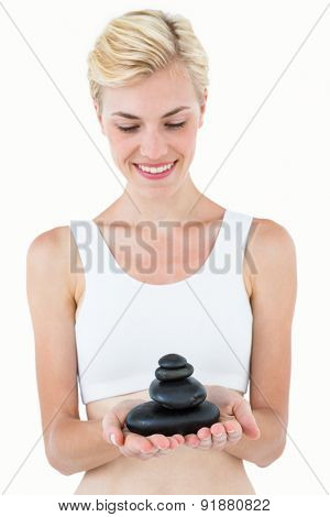 Fit woman holding stones on white background