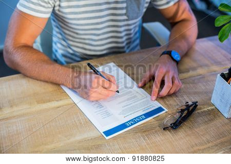 Man writing curriculum vitae at his desk