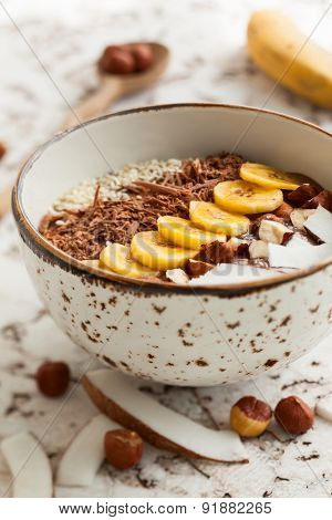 Chocolate hazelnut smoothie bowl topped with sliced banana, shredded coconut, chopped  chocolate, nuts and sesame seeds. Soft focus