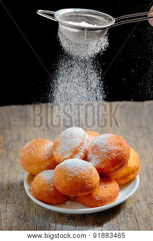 Pours Sugar Over Donuts