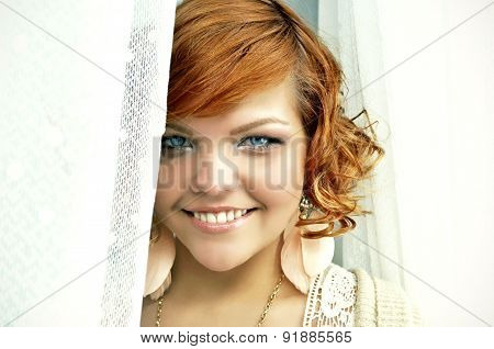 Stylish happy young woman with short curly red hair and bright blue eyes.
