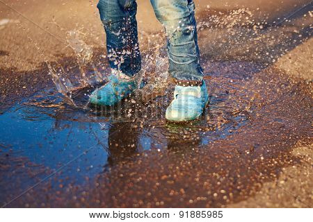 The Child Jumps In A Puddle