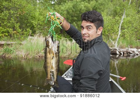 Young Hispanic Fisherman Holds Up A Stringer Of Walleyes