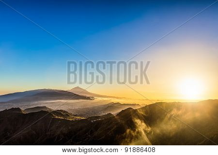 Sun And Clouds Over Mountains On Blue Sky
