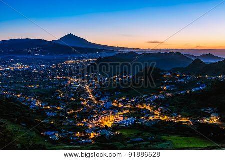 City With Illumination In Mountain Valley
