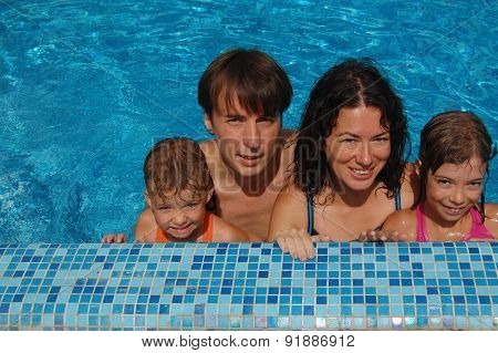 Happy family with two kids in swimming pool. Smiling parents and children on summer vacation