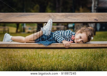Pleasure Little Girl Lying On Bench In A Park, Repose Or Relaxing In The Nature