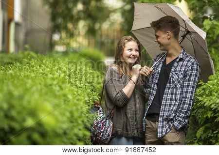 Boy and girl having fun in the Park under an umbrella.