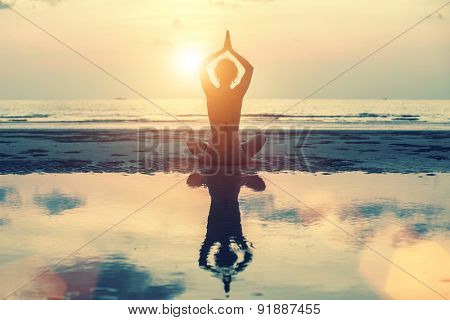 Meditation, yoga and fitness, a healthy lifestyle. Silhouette of a beautiful yoga woman at sunset in surreal colors.