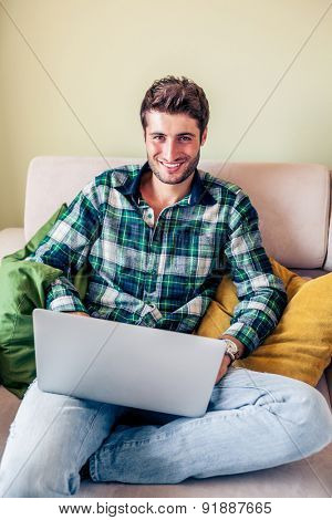 Handsome young man sitting on couch working on his laptop