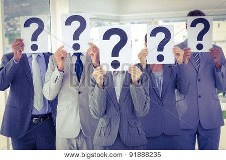 Business team holding question marks over face in the office