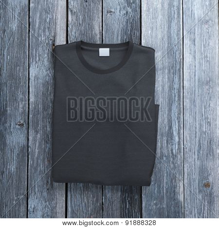 Black folded  t-shirt on wooden background