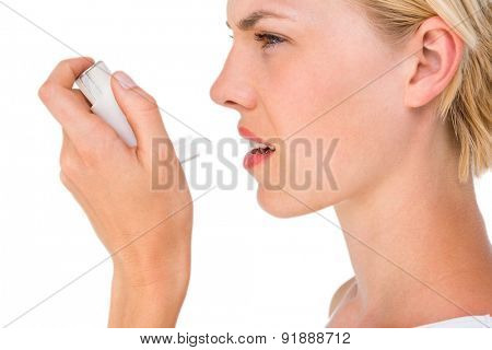 Asthmatic pretty blonde woman using inhaler on white background