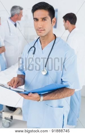 Doctor reading report with colleagues and patient behind