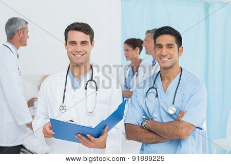 Report reading with colleagues and patient behind at hospital