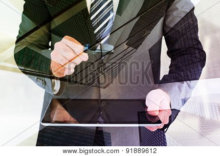 Businessman looking at tablet with magnifying glass against skyscraper