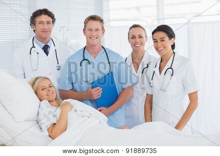 Team of doctor and patient looking at camera in hospital
