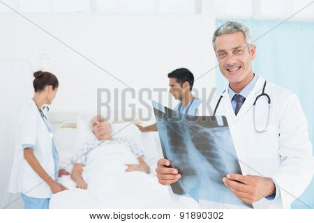 Male and female doctors examining x-ray with patient
